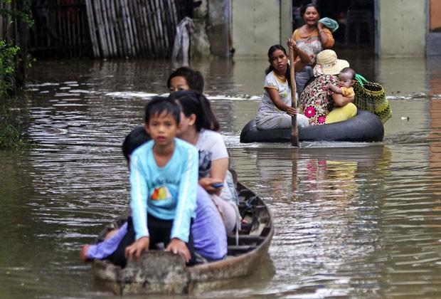 Famílias tentam deixar área alagada na região do Rio Mekong, em Phnom Penh, no Camboja, nesta terça-feira (1) (Foto: Samrang Pring/Reuters)