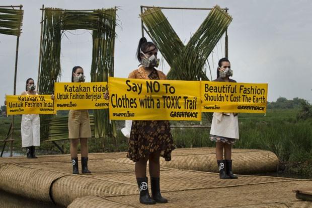 """Modelos seguram cartazes com os dizeres """"diga não à moda com produtos tóxicos"""" (Foto: Romeo Gacad/AFP)"""