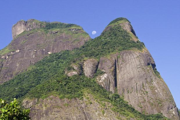 A Pedra da Gávea, vista da Barrinha, com uma lua crescente que aparece entre as duas pontas de granito. (Foto: © Mikael Castro)