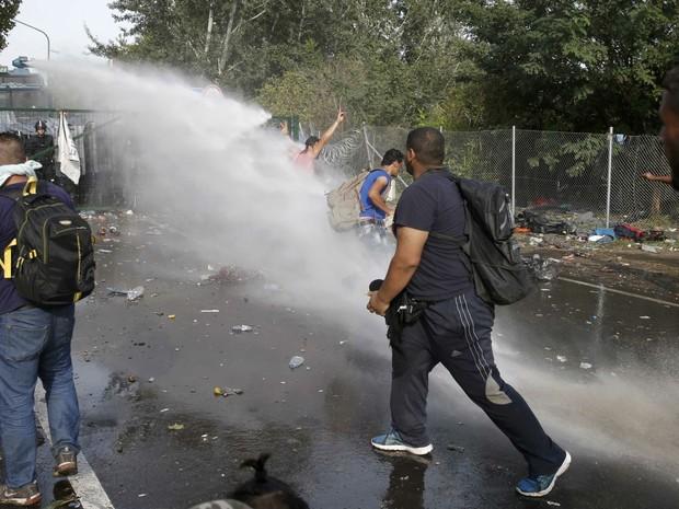Migrantes protestam na fronteira húngara e são reprimidos com jatos de água pela polícia (Foto: Marko Djurica/Reuters)