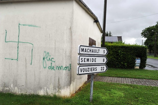 Pichação nazista é vista em muro de cermitério onde túmulos foram violados em Saint-Etienne-a-Arnes, na França (Foto: Alain Julien / AFP)