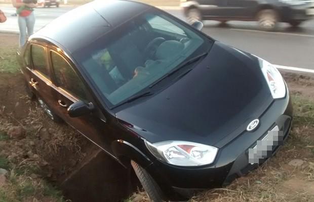 Carro ficou preso em bueiro às margens da BR-040, em Luziânia, Goiás (Foto: Reprodução/TV Anhanguera)