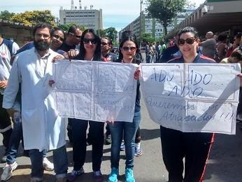 Servidores da saude seguram faixas em frente ao Hospital de Base (Foto: Isabella Calzolari/G1 DF)