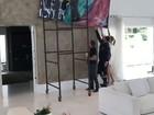 Ana Hickmann usa andaime para instalar quadros em sua sala