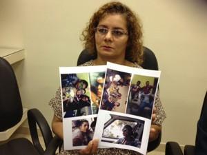 Mãe de David mostra fotos do filho durante entrevista nesta quarta (13) (Foto: Lívia Machado/G1)