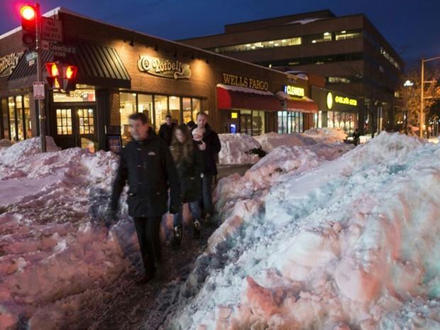 Pedestres passam por um monte de neve na região nordeste de Washington na noite de segunda-feira (25) (Foto: Mandel Ngan / AFP)