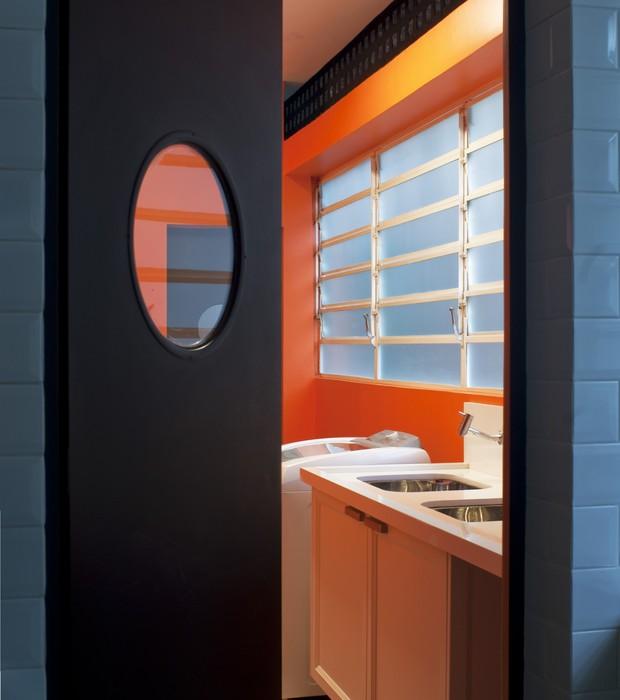 Sim, a área de serviço é laranja! As paredes foram pintadas com a cor General, da Suvinil. O armário de MDF Microtextura Branca se destaca na parede colorida. O piso é ladrilho hidráulico, da Ville Rose (Foto: Celia Weiss/Divulgação)