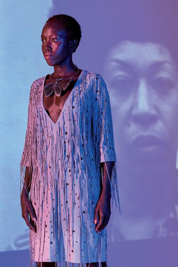 Com a ativista Angela Davis ao fundo, Kuoth usa vestido de camurça com tiras de veludo (R$ 43.120) e colar de prata (R$ 17.400) (Foto: Marco Piana)