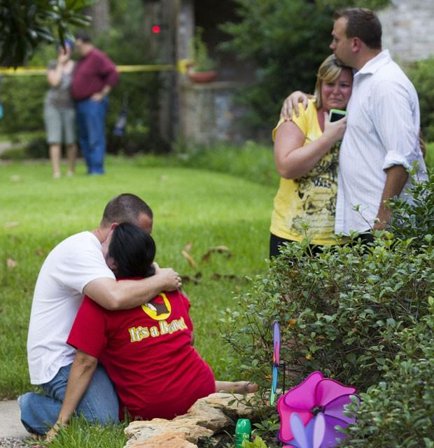 Vizinhos de casa onde homem matou seis pessoas nesta quarta-feira (9) - entre elas quatro crianças - choram após o crime  (Foto: Houston Chronicle, Brett Coomer/AP)