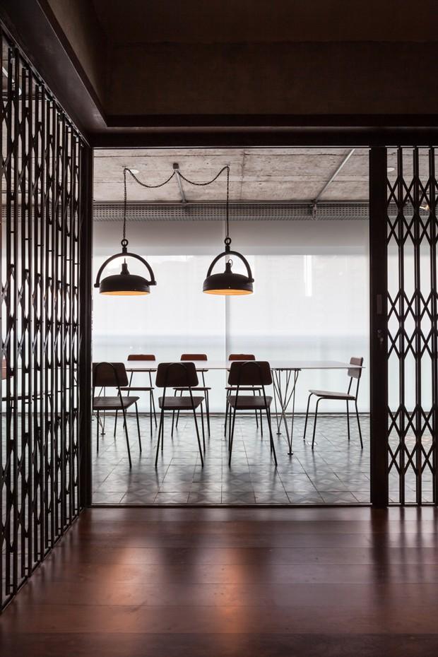 A sala de jantar ocupa o espaço da varanda com piso de ladrilho hidráulico e porta pantográfica (Foto:  Divulgação)