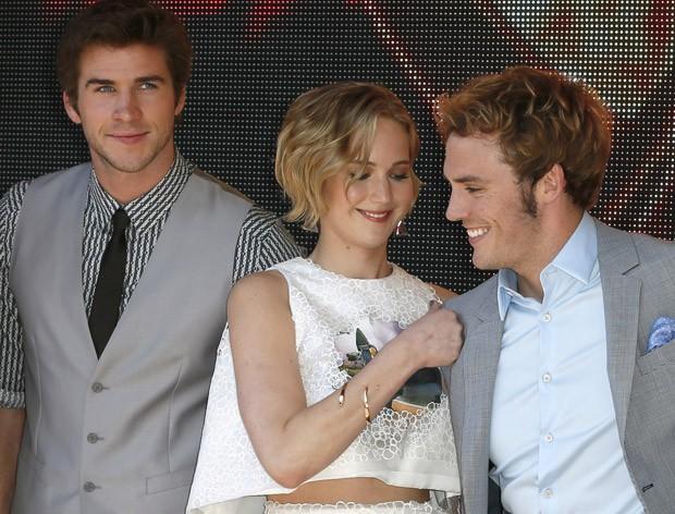 Jennifer Lawrence e os atores Liam Hemsworth ( esquerda) e Sam Clafin ( direita). (Foto: AP Images)