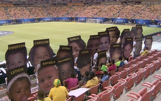 Voluntários seguram placas com rostos de crianças desaparecidas (Foto: Rede Amazônica)