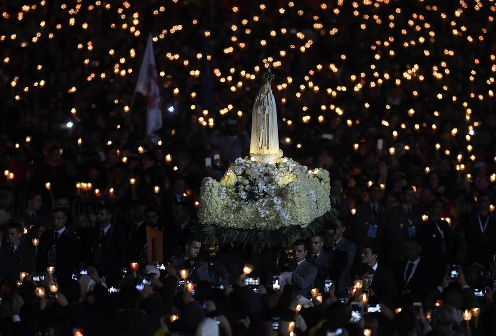 Fiéis carregam estátua da Virgem de Fétima nesta sexta-feira (12) durante visita papal (Foto: TIZIANA FABI / AFP)