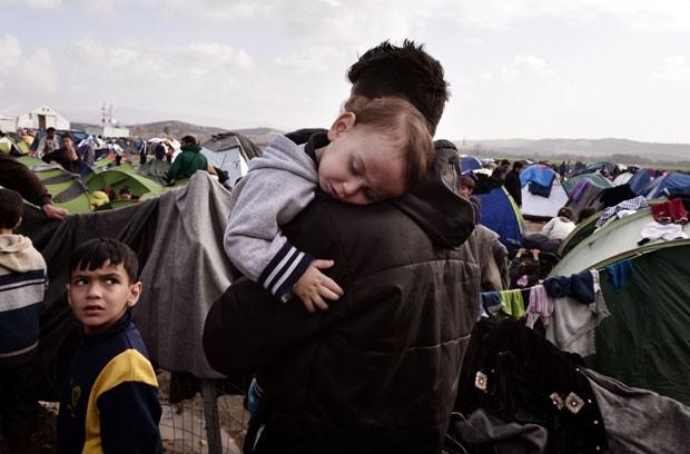 Bebê dorme nos braços de um homem em um acampamento de refugiados na fronteira da Grécia e Macedônia (Foto: Louisa Gouliamaki/AFP)