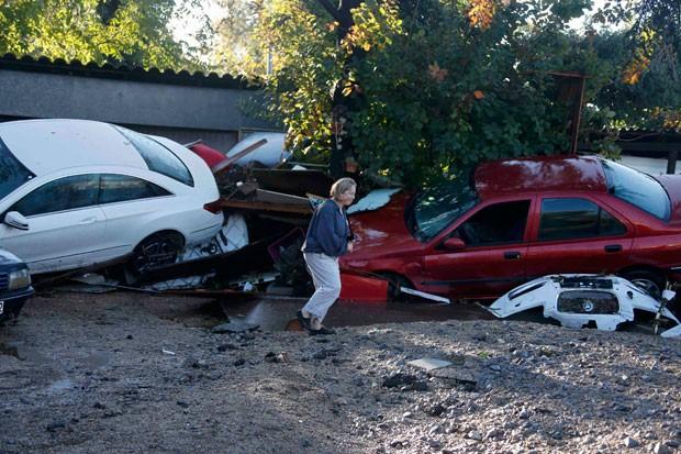 Mulher anda por carros danificados após inundação em Biot, na França, neste domingo (4) (Foto: Eric Gaillard/Reuters)