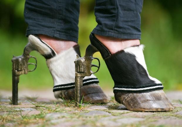 Iris Schieferstein criou um sapato feito com cascos de cavalo e revólveres.  (Foto: Patrick Pleul/AFP)