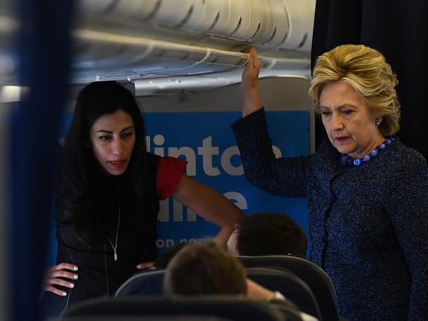A candidata democrata Hillary Clinton conversa nesta sexta-feira (28) com equipe ao lado da assessora Huma Abedin dentro do avião de campanha no Aeroproto do Condado de Westchester, no estado de Nova York (Foto: Jewel SAMAD / AFP)