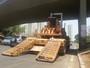 Retroescavadeira cai de caminhão e fica tombada em faixa da EPTG, no DF
