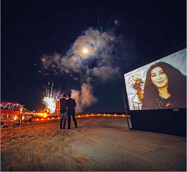 Colton Haynes e o noivo com um telão com a presença de Cher (Foto: Instagram)