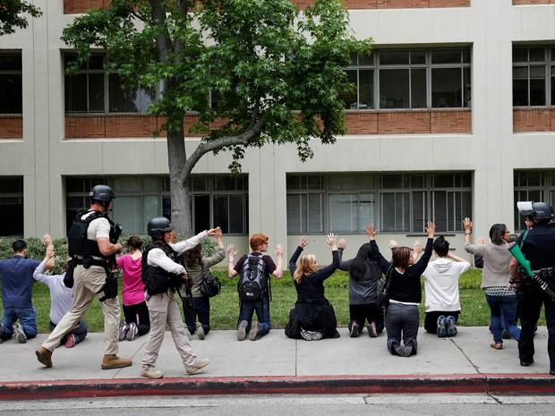 Pessoas se ajoelham para serem revistadas por policiais durante busca por atirador no campus da UCLA, Universidade da Califórnia em Los Angeles, EUA (Foto: Patrick T. Fallon/Reuters)