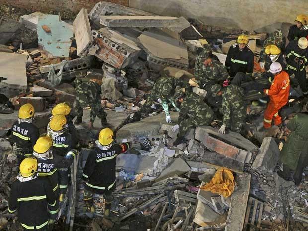 Equipes de resgate procuram por sobreviventes entre os escombros de um imóvel que ruiu na China, matando 17 pessoas (Foto: Reuters)