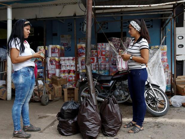 Pessoas ficam de olho nas sacolas levadas pela rua para saber onde achar certos produtos (Foto: Reuters/Carlos Garcia Rawlins)