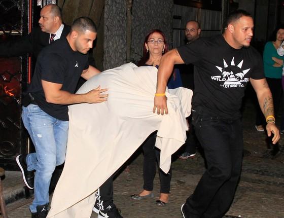 Para despistar os paparazzi, Bieber deixa a termas Centauros, na última vez que esteve no Rio, enrolado em um lençol (Foto: Reprodução)