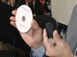 Delegado mostra CD com gravações e chaveiro usado para fazer vídeos íntimos. (Foto: Juliene Katayama/G1 MS)