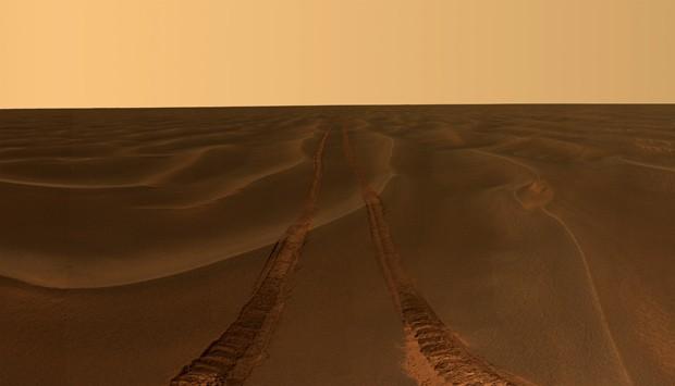 Imagem mostra os rastros de jipe desapaercendo no horizonte marciano; foto faz parte de exposição sobre veículos que exploraram Marte (Foto: AP Photo/NASA/JPL-Caltech/Cornell University)