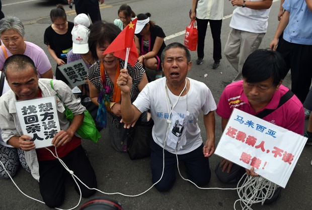 Parentes de passageiros do voo MH370 aguardam para falar com oficiais malaios em Pequim nesta sexta-feira (7) (Foto: Greg Baker/AFP)