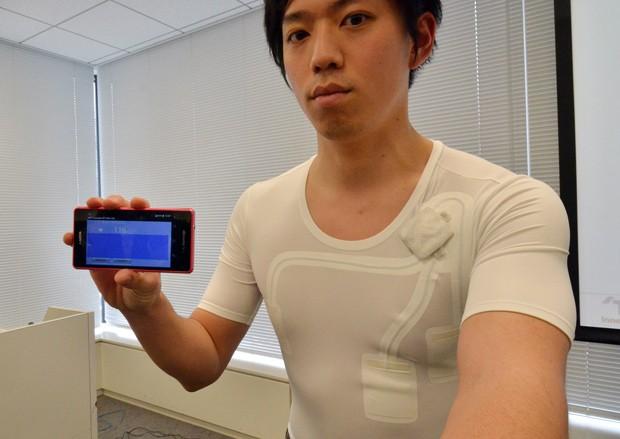 Homem demonstra funcionamento de camiseta com tecido 'hitoe' (Foto: AFP Photo/Yoshikazu Tsuno)
