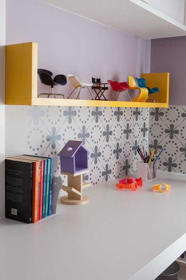 Prateleira amarela com miniaturas de cadeiras, e papel de parede estampado na parede lilás no apartamento da advogada Fabiana Salvadori, projetado pela arquiteta Andrea Murao (Foto: Lufe Gomes/Editora Globo)