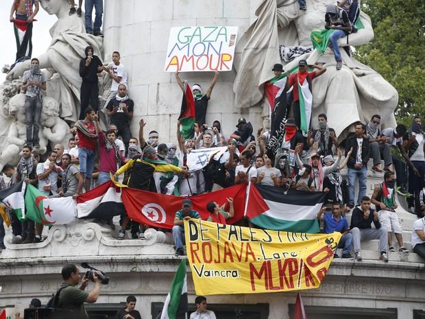 Manifestantes pró-palestinos sobem no monumento da República, em Paris, durante manifestação neste sábado (26) (Foto: Kenzo Tribouillard/AFP)