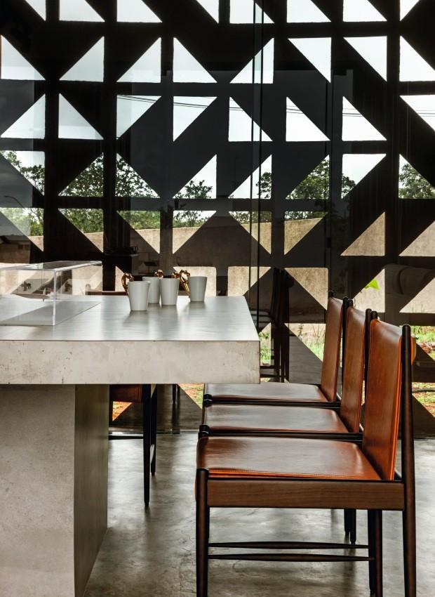 Sala de jantar. A mesa desenhada pelo escritório, revestida de porcelanato, harmoniza-se com as cadeiras de Sergio Rodrigues, da Hill House. Ao fundo, pode-se observar o desenho triangular dos cobogós (Foto: Edgard Cesar / Divulgação)