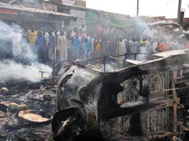 Veículo pega fogo depois de explosão de bomba nesta terça (1º) em mercado na cidade de Maiduguri, na Nigéria (Foto: AFP PHOTO/STRINGER)