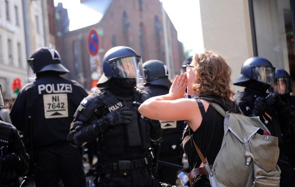 Manifestante grita palavras de ordem diante de policial durante protesto em Hamburgo, na Alemanha, nesta sexta-feira (7) (Foto: Steffi Loos / AFP)