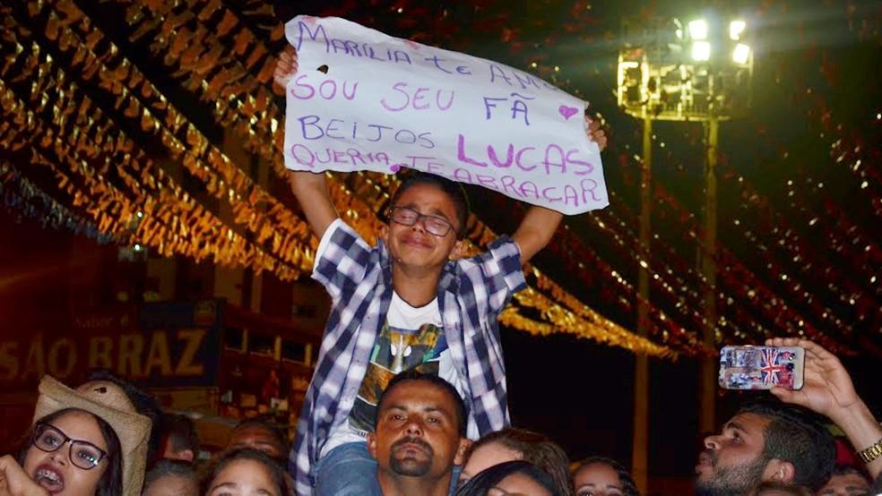 Fã-mirim de Marília Mendonça, Lucas, de nove anos, assistiu ao show nos ombros do pai e segurou cartaz para a cantora (Foto: Kamylla Lima/G1)