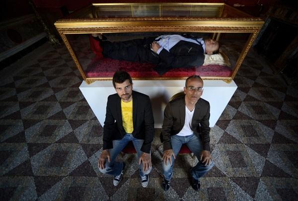 Os artistas italianos, Antonio Garullo e Mario Ottocento, posam em frente a obra exposta em Roma (Foto: Filippo Monteforte/AFP)