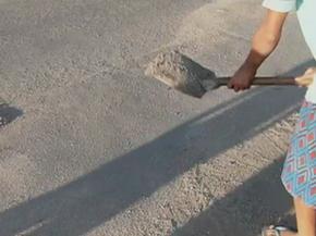 Crianças utilizam areia para tapar os buracos (Foto: Reprodução/TV Asa Branca)
