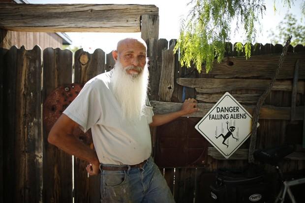 Roy Lohr posa ao lado de placa 'Perigo: queda de alienígenas' em frente a sua casa em Truth or Consequences, no estado do Novo México (EUA) (Foto: Lucy Nicholson/Reuters)