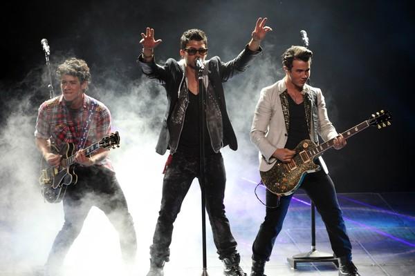 Os três irmãos do grupo Jonas Brothers durante um show (Foto: Getty Images)