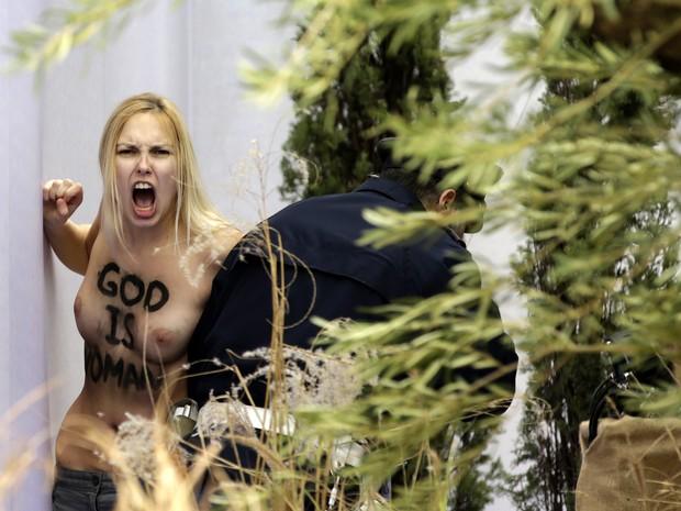 Integrante do femen estava com os seios nus e mostrava palavra God no corpo (Foto: VINCENZO LIVIERI / AFP)