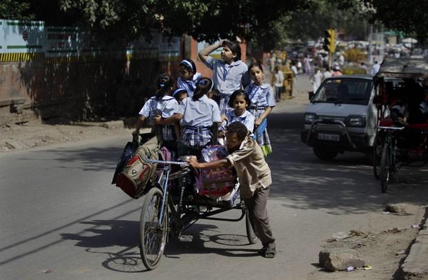 Indiano empurra triciclo conhecido como rickshaw lotado de estudantes. (Foto: Altaf Qadri/AP)