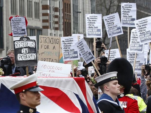 O caixão de Thatcher passa por pessoas contrárias às políticas aplicadas pela ex-premiê levantando cartazes em um protesto durante a cerimônia (Foto: Justin Tallis/AFP)