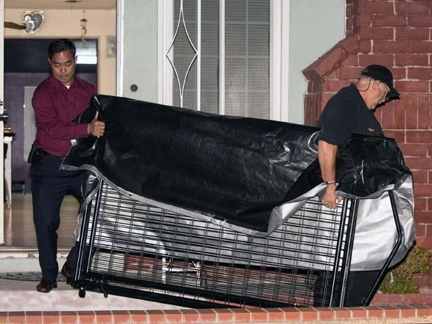 Detetives retiram jaula de residência em Anaheim, na California. A polícia suspeita de que menino de 11 anos ficava preso  (Foto: AP Photo/Kevin Warn)