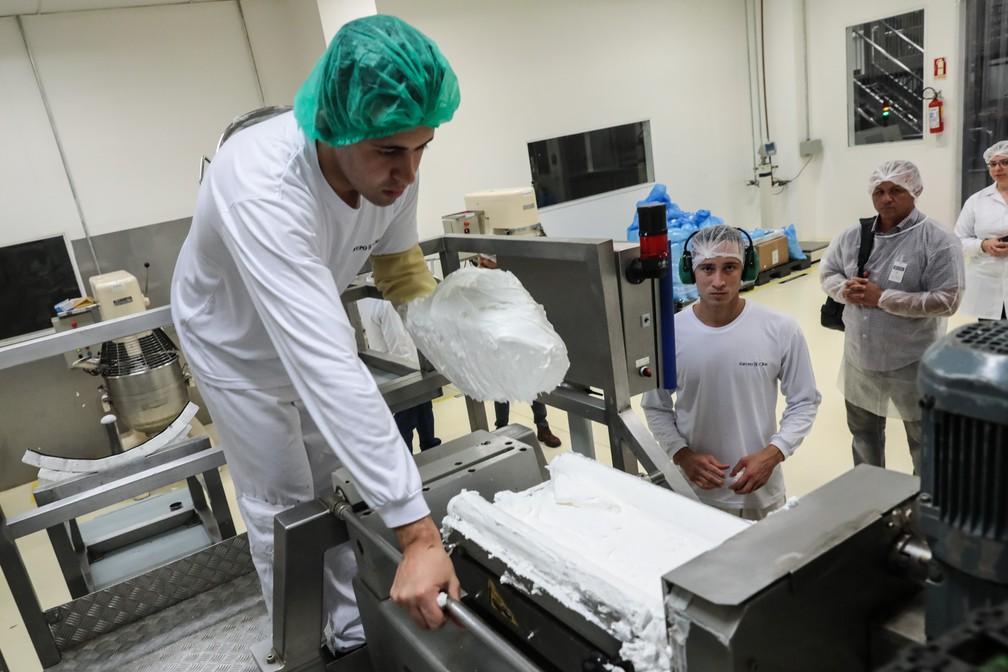 Com uma luva cobrindo boa parte do braço, o funcionário Jeferson Miguel retira o marshmallow do tacho e o coloca em uma máquina para ser despejado sobre biscoitos wafer e então receber banho de chocolate para se transformar em um dos bombons mais conhecidos da marca, o Nhá Benta (Foto: Fábio Tito/G1)