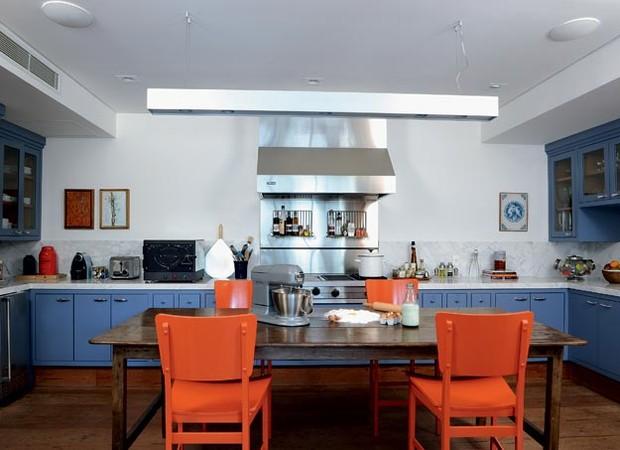 """Aberta para a sala de jantar, a cozinha gourmet tem o mesmo piso de madeira Angelim de demolição da área social. Em forma de """"U"""", possui armários de laca azul K017, da Sayerlack, em todas as paredes. nas laterais, os armários altos têm portas de vidro. Tu (Foto: Marcelo Magnani)"""