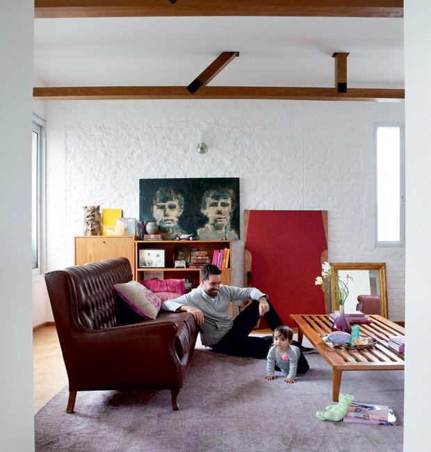 Thiago Passos brinca com sua filha Olivia na sala de estar com almofadas da Empório Beraldin e da Donatelli. O sofá restaurado veio do bazar da Unibes, e a mesa de centro é feita a partir de um estrado. Tapete da By Kamy. Ao fundo, tela de Rogério Pinto. Objetos da Loja Teo e Benedixt. No chão, tela de Feres Khoury, na Arterix. Na pág. anterior, o detalhe exibe raquete de tênis que pertencia ao avô de Thiago (Foto: Lufe Gomes/Editora Globo)