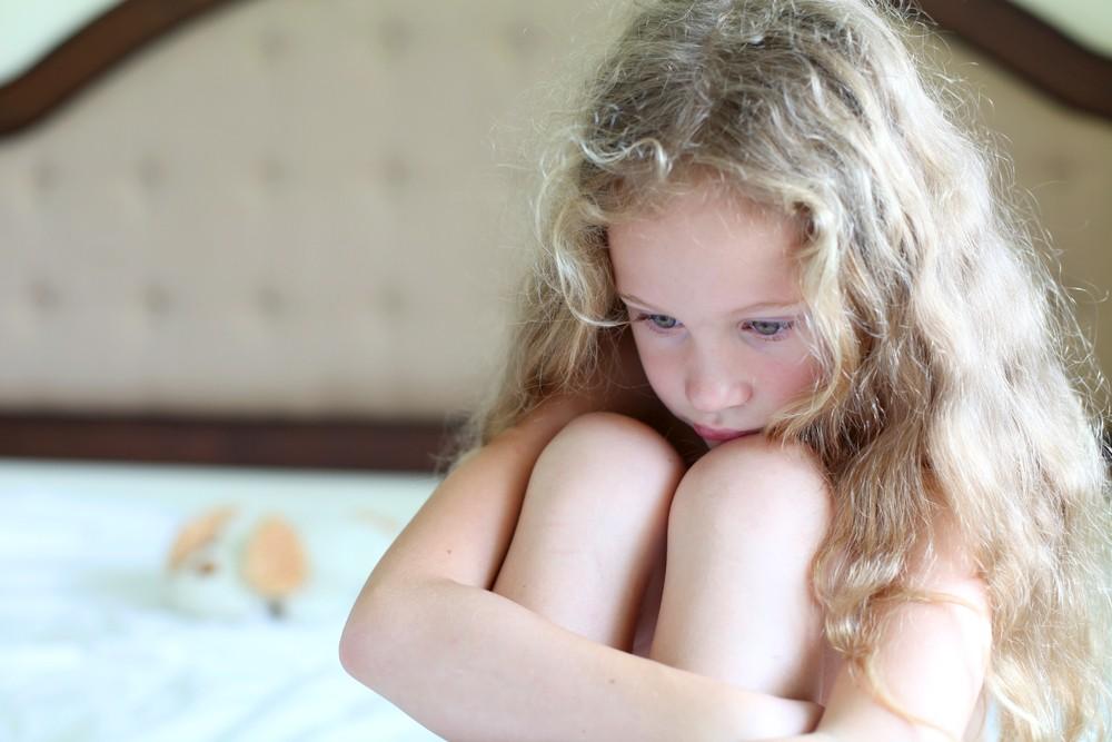 Criança triste com dor nas pernas  (Foto: Shutterstock)