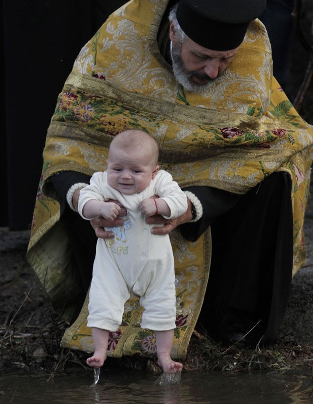 Padre ortodoxo batiza criança nas águas do rio  Tundzha, na Bulgária (Foto: Valentina Petrova/AP)